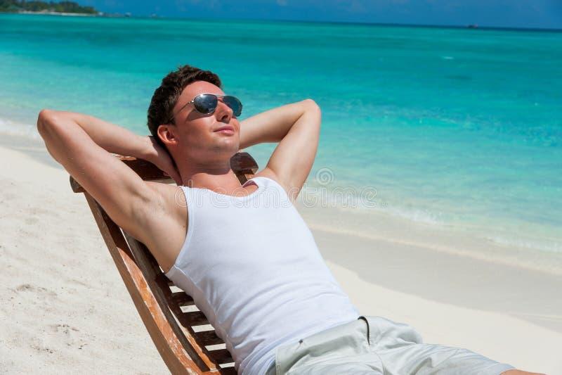 Άτομο στην καρέκλα που κάνει ηλιοθεραπεία στην παραλία κοντά στον ωκεανό στοκ εικόνα