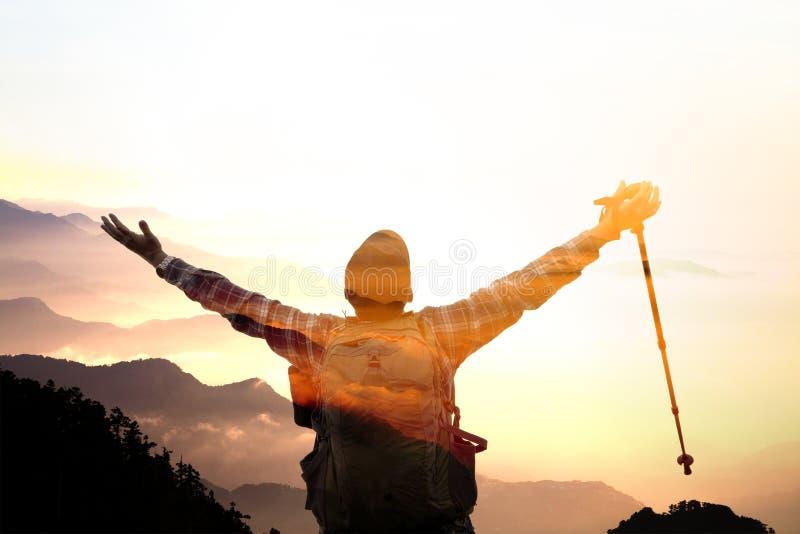 Άτομο στην κορυφή της ανατολής προσοχής βουνών στοκ φωτογραφία