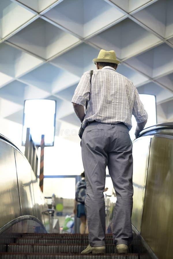 Άτομο στην κυλιόμενη σκάλα στο ψωνίζοντας κέντρο λεωφόρων ή υπόγεια στοκ φωτογραφίες