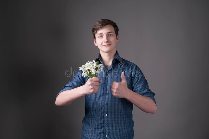 Άτομο στην μπλε ανθοδέσμη εκμετάλλευσης πουκάμισων με τα snowdrops, που εξετάζουν τη κάμερα και που φυλλομετρούν επάνω στο γκρίζο στοκ φωτογραφίες με δικαίωμα ελεύθερης χρήσης