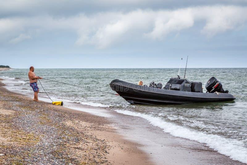 Άτομο στην παραλία που τραβά ένα σχοινί για να κρατήσει τη βάρκα του στοκ φωτογραφία με δικαίωμα ελεύθερης χρήσης