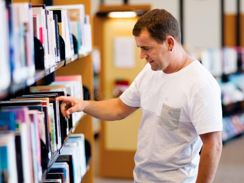 Άτομο στη βιβλιοθήκη στοκ φωτογραφία με δικαίωμα ελεύθερης χρήσης