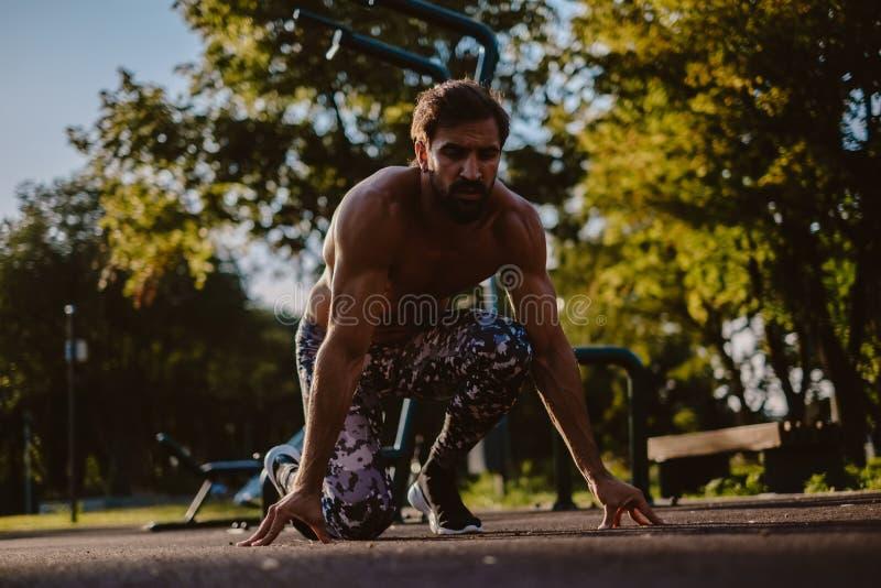 Άτομο στη θέση έναρξης τεσσάρων σημείου στην υπαίθρια γυμναστική στοκ φωτογραφία