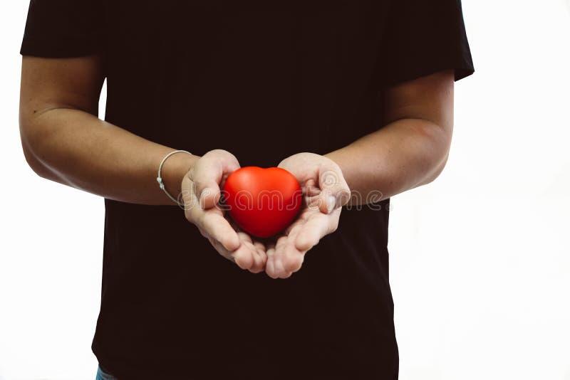Άτομο στη μαύρη μπλούζα που κρατά την κόκκινη καρδιά στο χέρι του, αντίγραφο διαστημικό φ στοκ φωτογραφίες με δικαίωμα ελεύθερης χρήσης