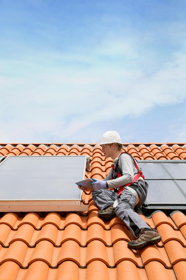 Άτομο στη στέγη που εγκαθιστά τα ηλιακά πλαίσια στοκ φωτογραφία