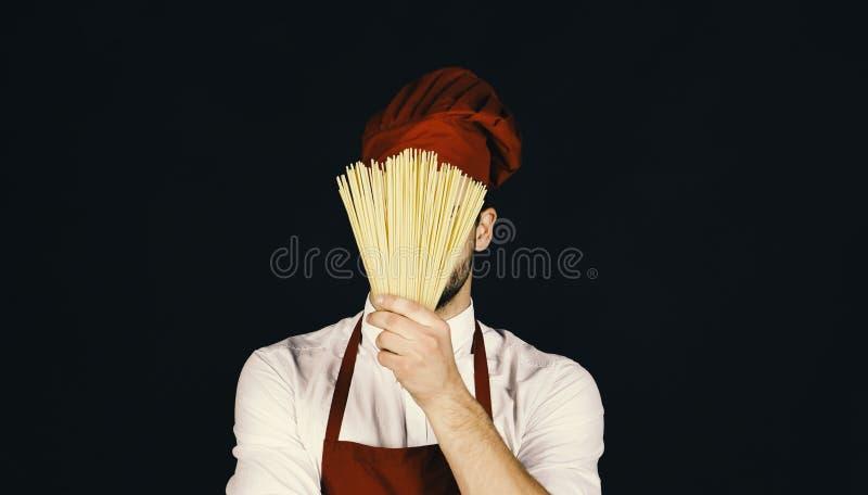 Άτομο στις δορές καπέλων και ποδιών μαγείρων πίσω από τα ζυμαρικά Ο αρχιμάγειρας με το κρυμμένο πρόσωπο κρατά τη δέσμη των μακαρο στοκ φωτογραφία με δικαίωμα ελεύθερης χρήσης