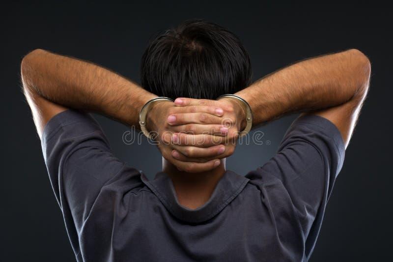 Άτομο στις χειροπέδες στην γκρίζα ανασκόπηση στοκ φωτογραφία