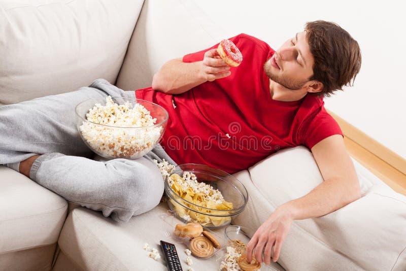 Άτομο στον καναπέ με τις απολαύσεις στοκ εικόνες