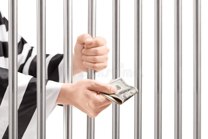 Άτομο στους φραγμούς και το δόσιμο φυλακών εκμετάλλευσης φυλακών της δωροδοκίας στοκ φωτογραφία