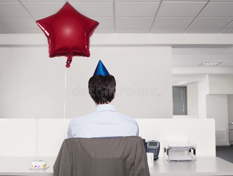 Άτομο στο καπέλο κόμματος με την εργασία μπαλονιών στην αρχή στοκ φωτογραφία με δικαίωμα ελεύθερης χρήσης