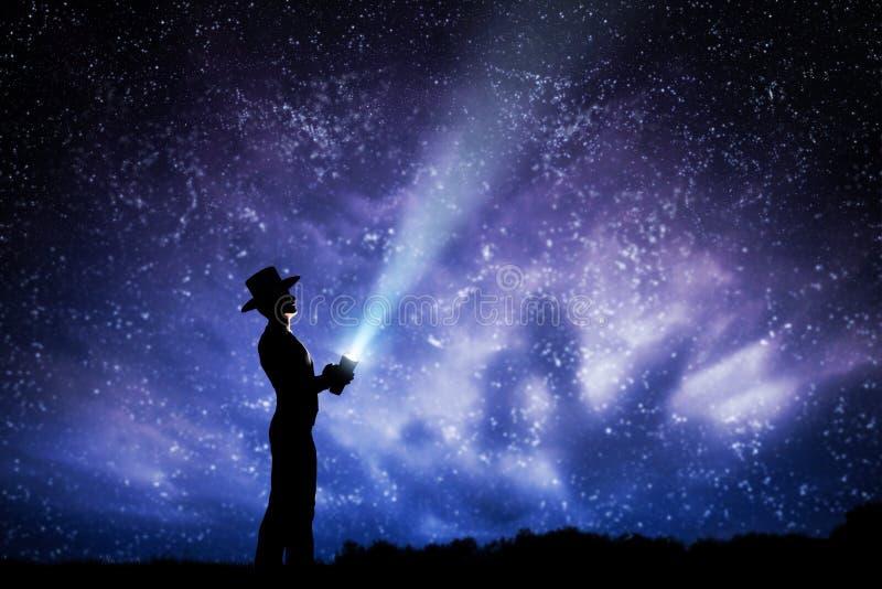 Άτομο στο καπέλο που ρίχνει την ελαφριά ακτίνα επάνω το σύνολο νυχτερινού ουρανού των αστεριών Για να εξερευνήσετε, ονειρευτείτε, απεικόνιση αποθεμάτων