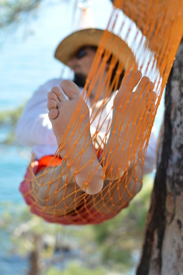 Άτομο στο καπέλο σε μια αιώρα στο δέντρο πεύκων στην Κριμαία μια θερινή ημέρα στοκ εικόνες με δικαίωμα ελεύθερης χρήσης