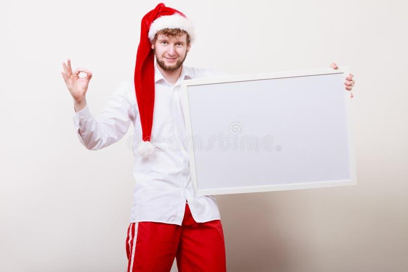 Άτομο στο καπέλο santa με το κενό έμβλημα διάστημα αντιγράφων στοκ φωτογραφία με δικαίωμα ελεύθερης χρήσης