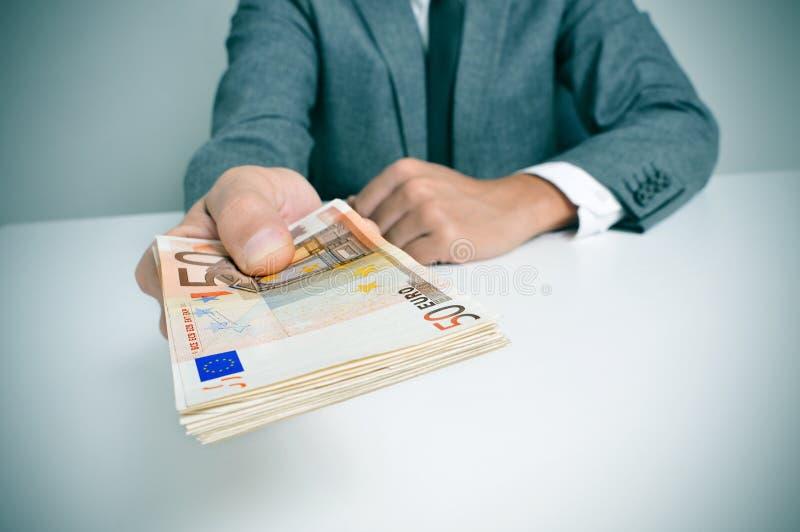 Άτομο στο κοστούμι με ένα wad των ευρο- λογαριασμών στοκ εικόνες