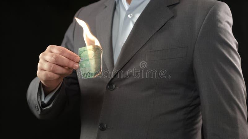 Άτομο στο κοστούμι που καίει το λογαριασμό εκατό ευρώ, οικονομική κρίση, έννοια πτώχευσης στοκ φωτογραφία