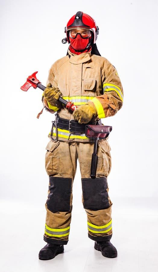 Άτομο στο κοστούμι του τσεκουριού εκμετάλλευσης πυροσβεστών στοκ φωτογραφία με δικαίωμα ελεύθερης χρήσης