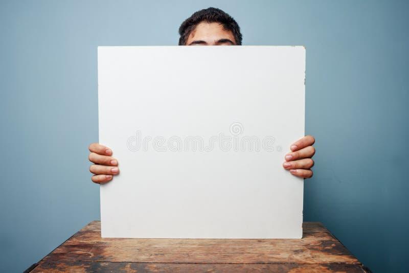 Άτομο στο κρύψιμο γραφείων πίσω από έναν λευκό πίνακα στοκ φωτογραφίες