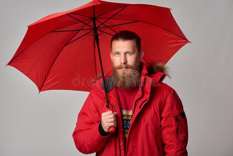 Άτομο στο κόκκινο χειμερινό σακάκι που στέκεται με την ομπρέλα στοκ εικόνα