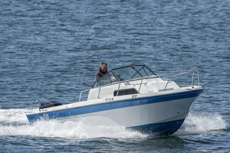 Άτομο στο μικρό ταχύπλοο σκάφος καμπινών στον ποταμό Acushnet στοκ φωτογραφία