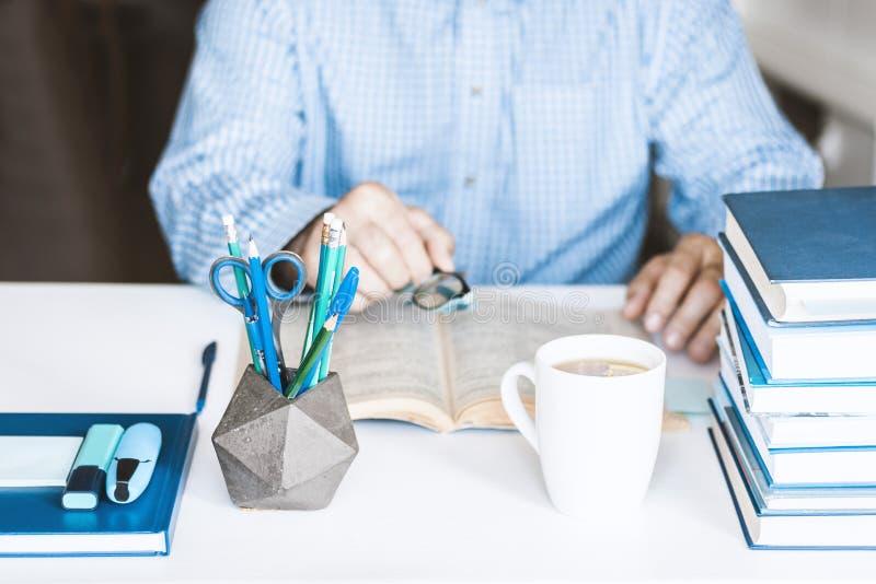 Άτομο στο μπλε βιβλίο ανάγνωσης πουκάμισων στο σύγχρονο μοντέρνο χώρο εργασίας με τις προμήθειες γραφείων και βιβλία, έννοια εργα στοκ εικόνα