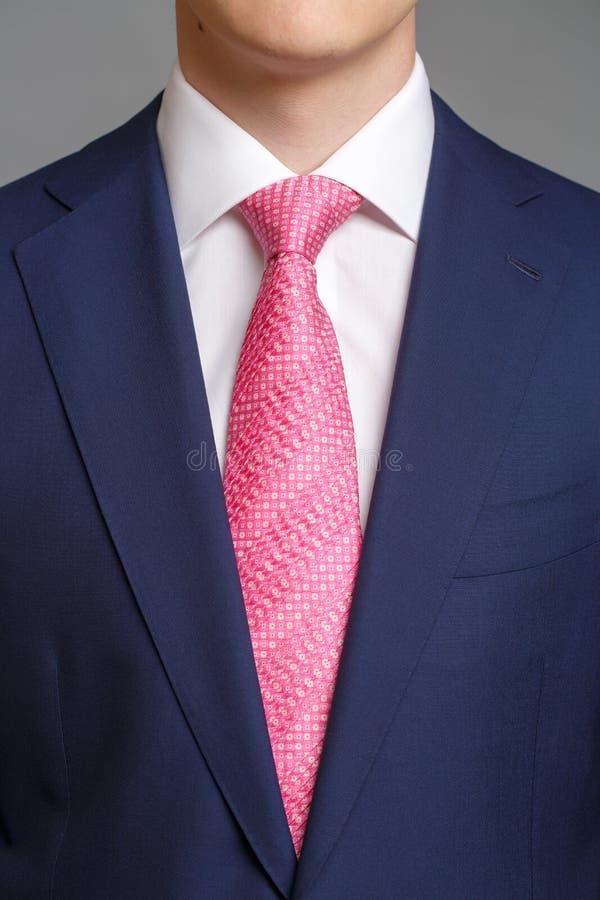 Άτομο στο μπλε σμόκιν με το ρόδινο δεσμό στοκ εικόνα