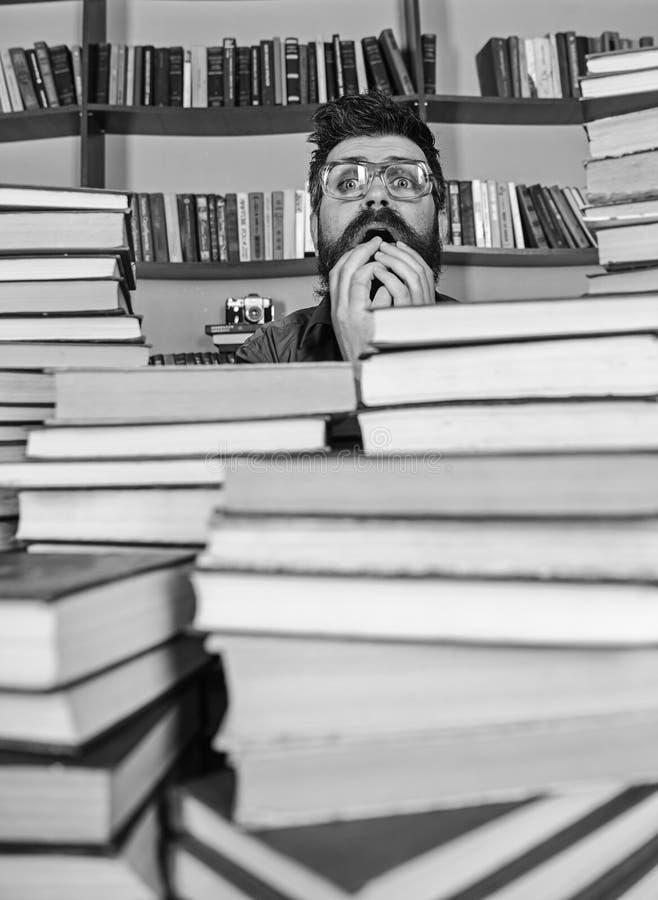 Άτομο στο νευρικό πρόσωπο μεταξύ των σωρών των βιβλίων στη βιβλιοθήκη, ράφια στο υπόβαθρο Ο δάσκαλος ή ο σπουδαστής με τη γενειάδ στοκ φωτογραφίες με δικαίωμα ελεύθερης χρήσης