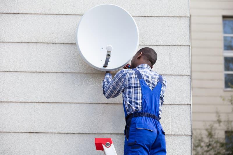 Άτομο στο ομοιόμορφο δορυφορικό πιάτο TV συναρμολογήσεων στοκ εικόνες