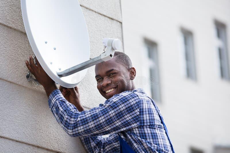Άτομο στο ομοιόμορφο δορυφορικό πιάτο TV συναρμολογήσεων στοκ φωτογραφία με δικαίωμα ελεύθερης χρήσης