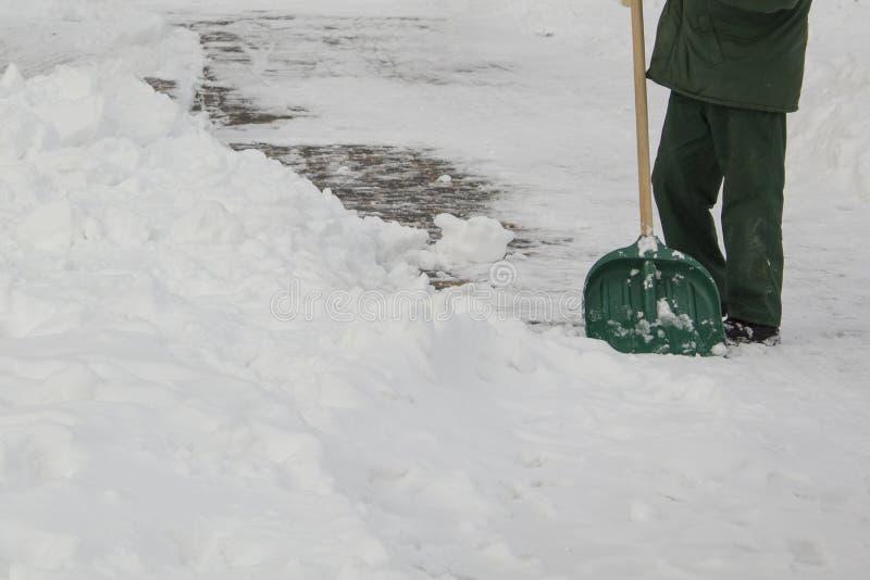Άτομο στο ομοιόμορφο καθαρίζοντας χιόνι με ένα φτυάρι στοκ φωτογραφίες