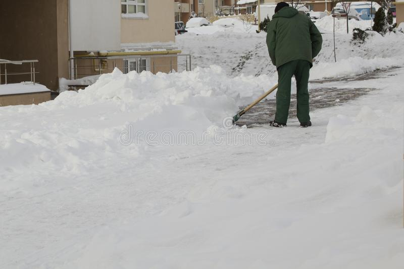 Άτομο στο ομοιόμορφο καθαρίζοντας χιόνι με ένα φτυάρι στοκ φωτογραφίες με δικαίωμα ελεύθερης χρήσης
