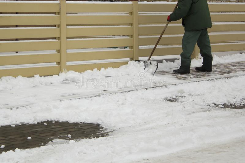 Άτομο στο ομοιόμορφο καθαρίζοντας χιόνι με ένα φτυάρι στοκ φωτογραφία με δικαίωμα ελεύθερης χρήσης