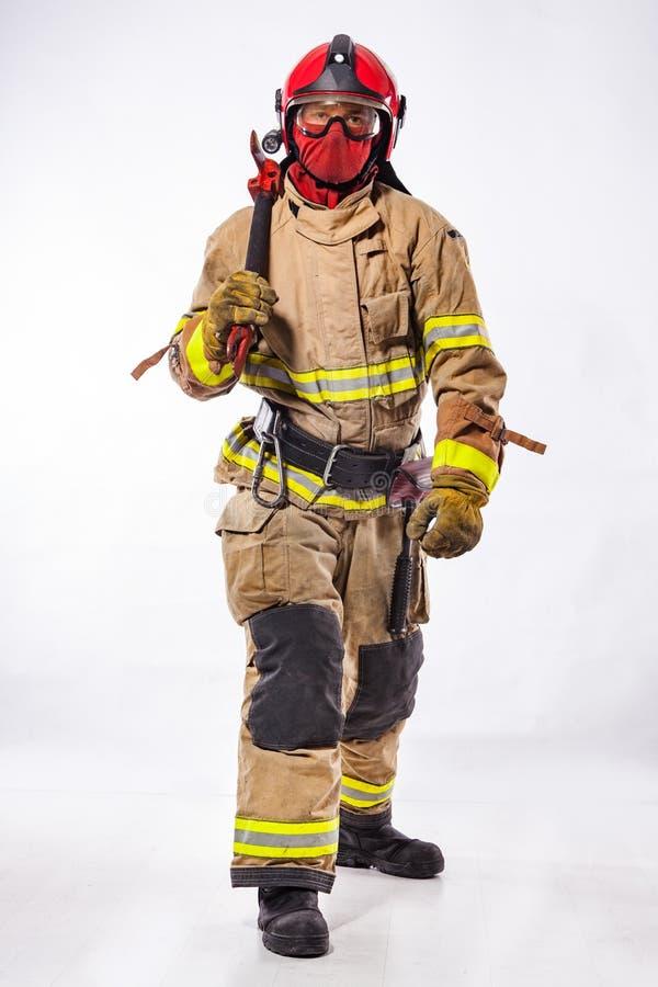Άτομο στο ομοιόμορφο τσεκούρι πυρκαγιάς εκμετάλλευσης στοκ εικόνες