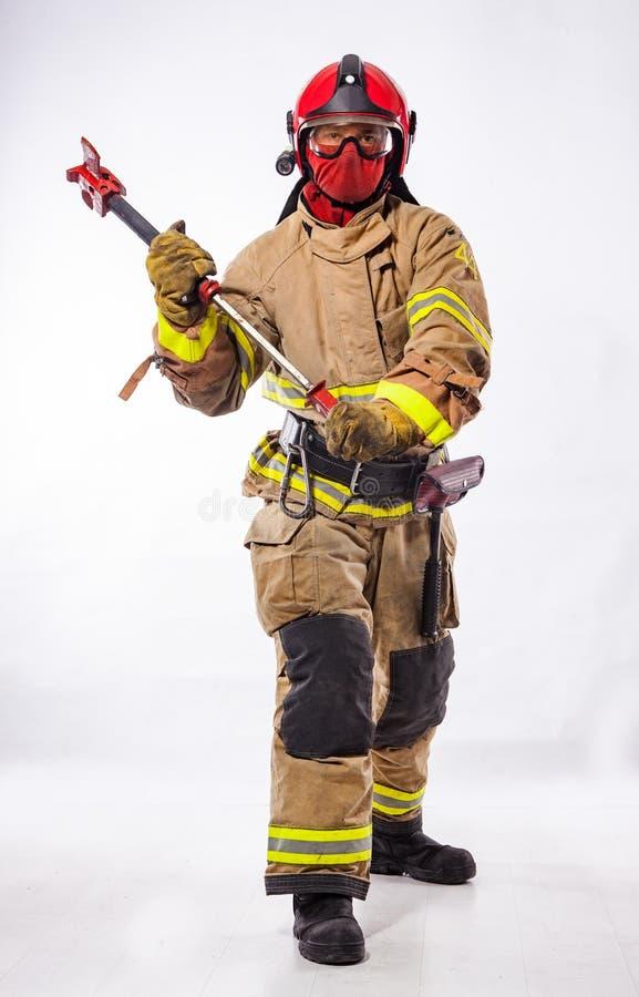 Άτομο στο ομοιόμορφο τσεκούρι πυρκαγιάς εκμετάλλευσης στοκ φωτογραφίες με δικαίωμα ελεύθερης χρήσης