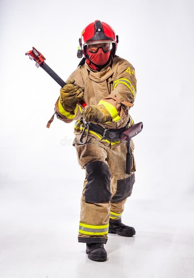 Άτομο στο ομοιόμορφο τσεκούρι πυρκαγιάς εκμετάλλευσης στοκ φωτογραφία με δικαίωμα ελεύθερης χρήσης
