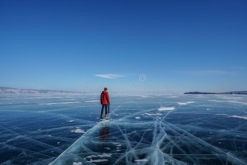 Άτομο στο πορτοκαλί τρίποδο καμερών εκμετάλλευσης ταξιδιού χειμερινών σακακιών στην παγωμένη Baikal λίμνη στο Ιρκούτσκ, Ρωσία το  στοκ φωτογραφία με δικαίωμα ελεύθερης χρήσης