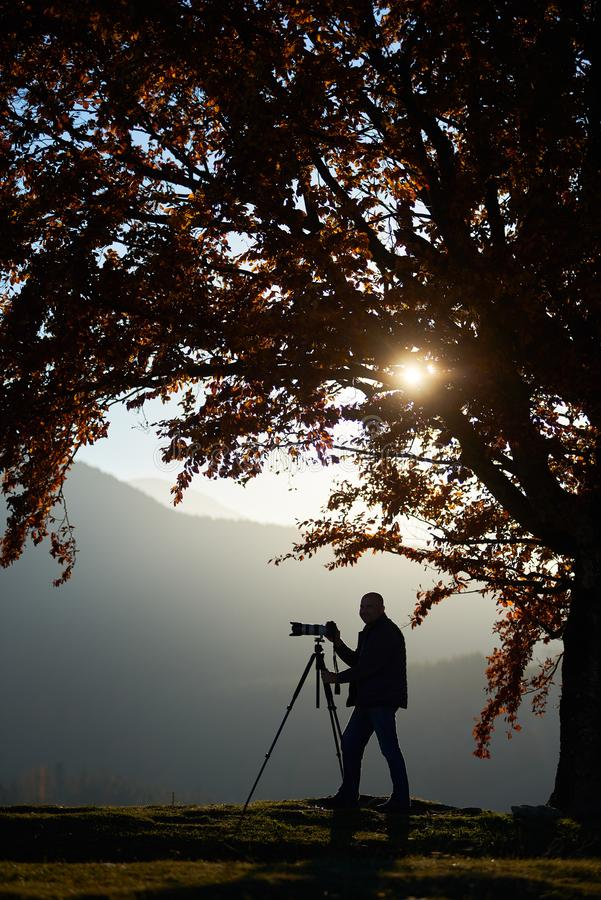 Άτομο τουριστών οδοιπόρων με τη κάμερα στη χλοώδη κοιλάδα στο υπόβαθρο του τοπίου βουνών κάτω από το μεγάλο δέντρο στοκ εικόνες