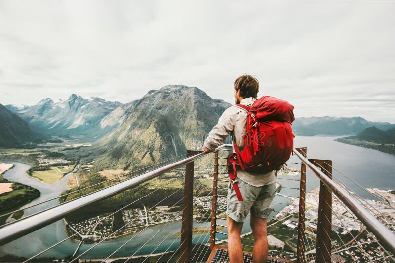 Άτομο τυχοδιωκτών με το κόκκινο σακίδιο πλάτης που απολαμβάνει το τοπίο βουνών στοκ φωτογραφία με δικαίωμα ελεύθερης χρήσης