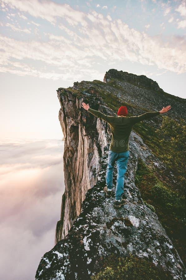 Άτομο τυχοδιωκτών στην κορυφογραμμή βουνών ακρών επάνω από τα σύννεφα στοκ φωτογραφία με δικαίωμα ελεύθερης χρήσης