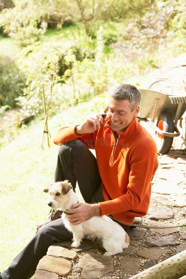 Άτομο υπαίθρια στο κινητό τηλέφωνο με το σκυλί στοκ φωτογραφία