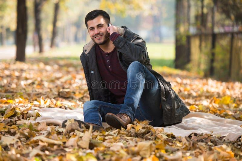 Άτομο φθινοπώρου που μιλά στο κινητό τηλέφωνο το φθινόπωρο στοκ φωτογραφία με δικαίωμα ελεύθερης χρήσης