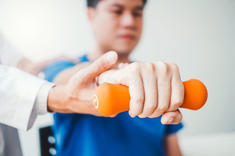 Άτομο φυσιοθεραπευτών που δίνει την άσκηση με τη θεραπεία αλτήρων για το βραχίονα και τον ώμο της αρσενικής υπομονετικής φυσικής  στοκ εικόνες