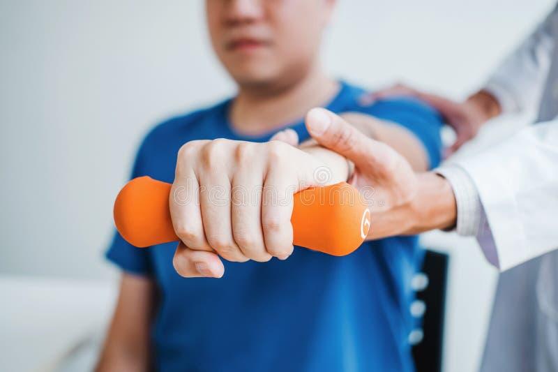 Άτομο φυσιοθεραπευτών που δίνει την άσκηση με τη θεραπεία αλτήρων για το βραχίονα και τον ώμο της αρσενικής υπομονετικής φυσικής  στοκ φωτογραφίες