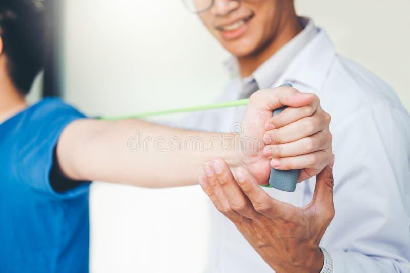 Άτομο φυσιοθεραπευτών που δίνει τη θεραπεία άσκησης ζωνών αντίστασης για το βραχίονα και τον ώμο της αρσενικής υπομονετικής φυσικ στοκ φωτογραφίες