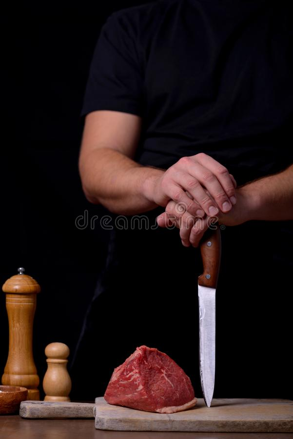Άτομο χεριών με το μαχαίρι και το ακατέργαστο βόειο κρέας στοκ εικόνα