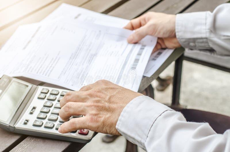 Άτομο χρησιμοποιώντας τον υπολογιστή και σκεπτόμενος για το κόστος με την πληρωμή των λογαριασμών στοκ εικόνα