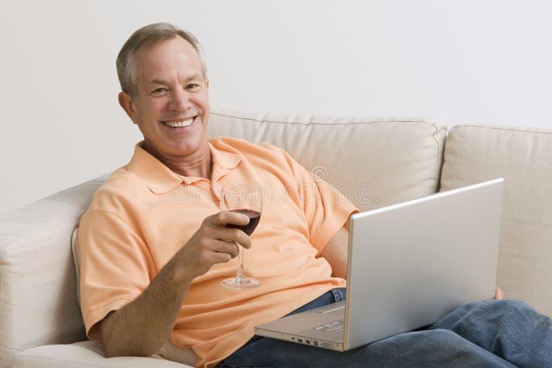 Άτομο χρησιμοποιώντας το lap-top και πίνοντας το κρασί στοκ εικόνες