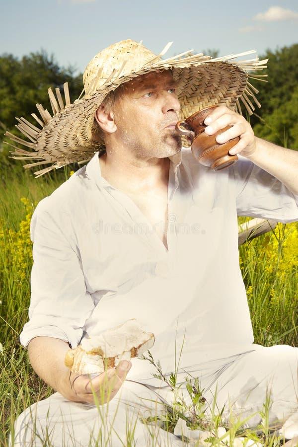 Άτομο χώρας στην κατανάλωση καπέλων αχύρου στην ηλιόλουστη ημέρα στοκ εικόνες