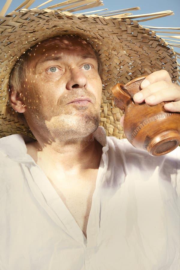 Άτομο χώρας στην κατανάλωση καπέλων αχύρου στην ηλιόλουστη ημέρα στοκ φωτογραφίες
