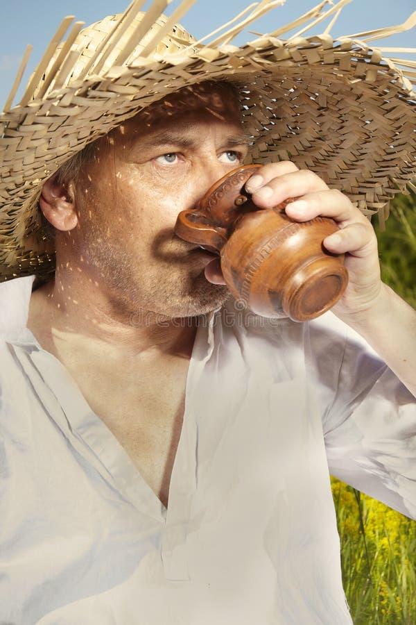Άτομο χώρας στην κατανάλωση καπέλων αχύρου στην ηλιόλουστη ημέρα στοκ φωτογραφία