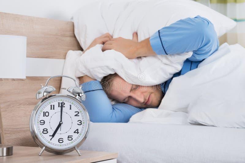 Άτομο ύπνου διαταραγμένο από το χτυπώντας ξυπνητήρι στοκ εικόνα